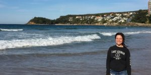 Picture of Megan Muccio on the beach in Australia with ocean waves in the background.