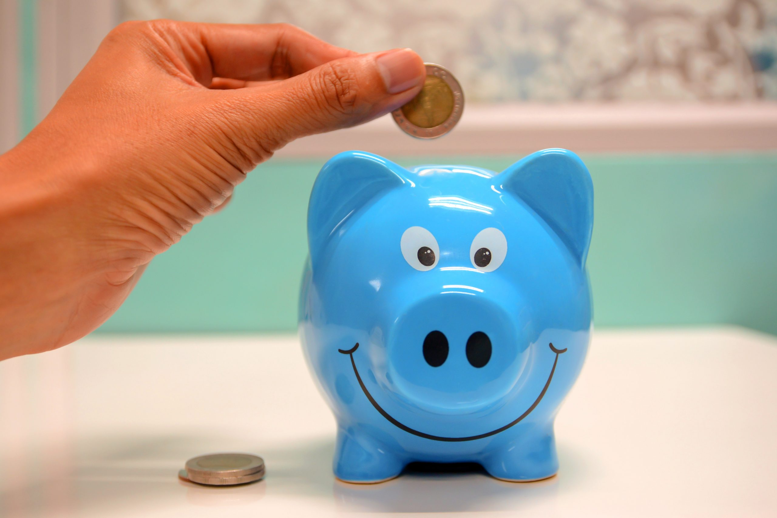 Hand dropping coin into a blue piggy bank
