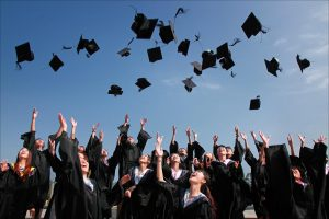 Teenagers in graduation gowns throwing their graduation hats
