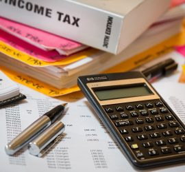 Stack of papers and book for Income taxes with calculator and pen - all documents used for tax preparation