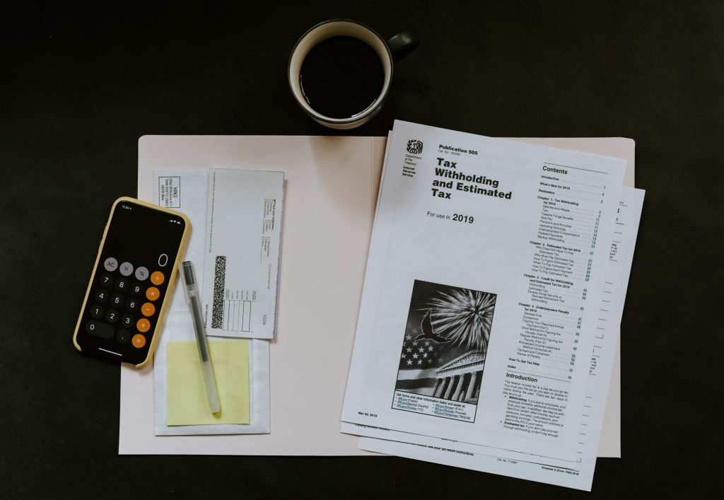 Tax paperwork spread on a desk with a calculator and pen next to it showing planning for taxes