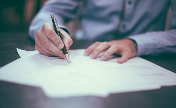 Hands writing to show someone preparing for tax meetings